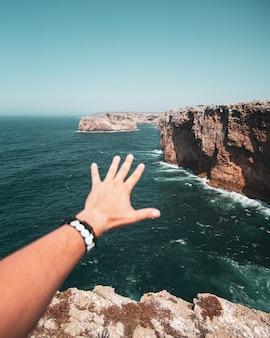Hand van een man die reikt naar de kliffen en de zee
