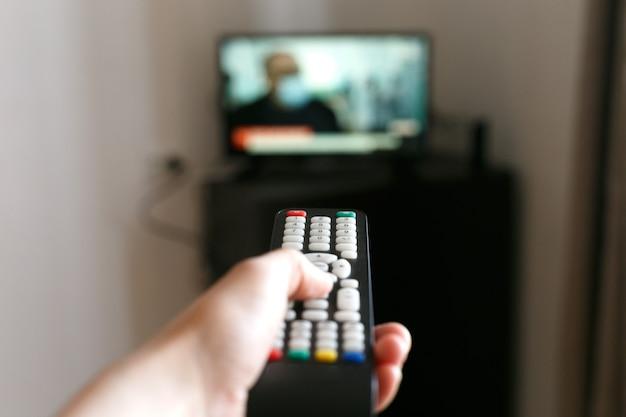 Hand van een man met een afstandsbediening van de tv.