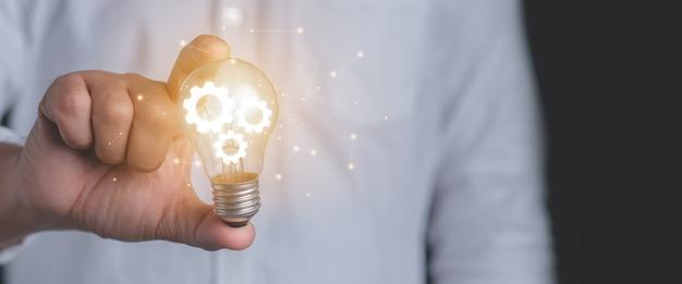 Hand van een man met een verlichte gloeilamp. idee innovatie en inspiratie concept.
