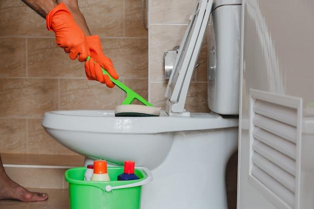 Hand van een man met oranje rubberen handschoenen wordt gebruikt om polijsten om te zetten in een toilet.