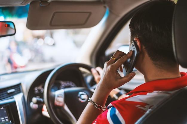 Hand van een man praten aan de telefoon tijdens het besturen van een auto