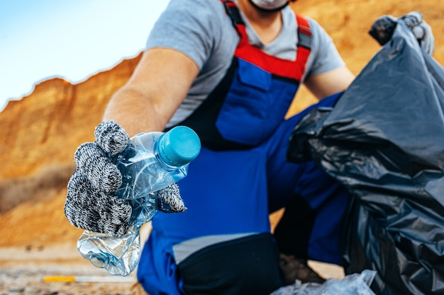 Hand van een man-vrijwilliger die plastic afval grijpt in een afvalzak die het strand van dichtbij opruimt