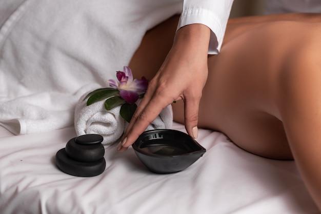 Hand van een massagetherapeut die een kom met massageolie neemt