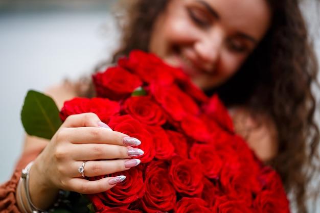 Hand van een meisje met een close-up van een trouwring op een boeket rode rozen
