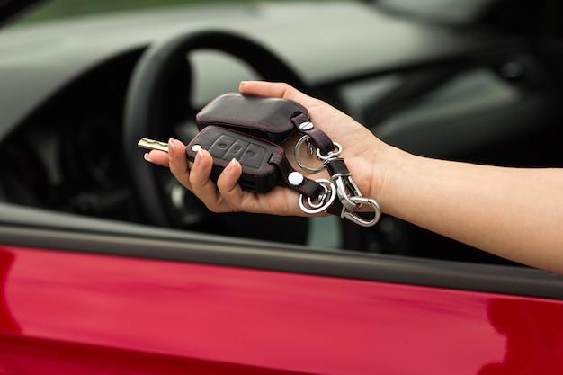 Hand van een meisje met een in hand autosleutel, op een rode autonachtergrond