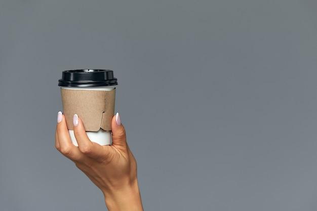Hand van een meisje met een papieren kopje koffie, grijze achtergrond goedemorgen, concept. lege plaats voor een inscriptie.