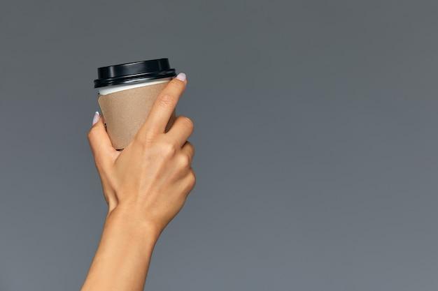 Hand van een meisje met een papieren kopje koffie, grijze ondergrond goedemorgen, concept