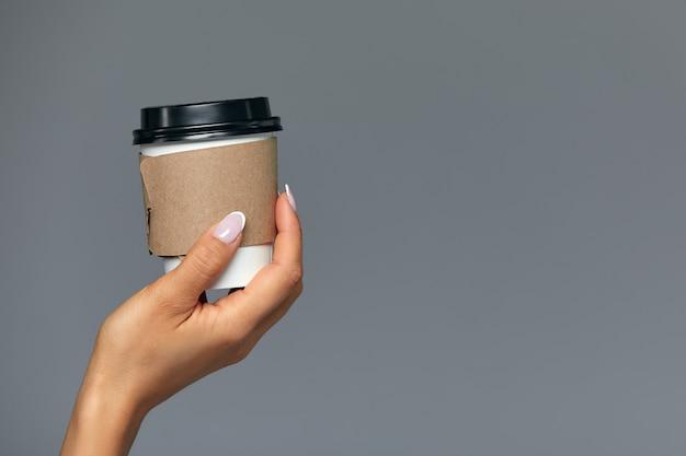 Hand van een meisje met een papieren kopje koffie