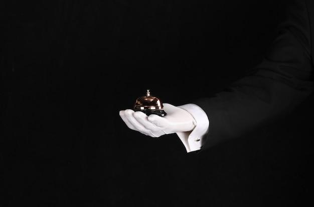 Hand van een ober met een dienstoproep op een zwarte achtergrond