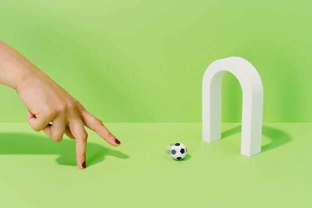 Hand van een onbekende vrouw die speelt met een voetbal op een doel op een groene achtergrond. voetbal en sportconcept.