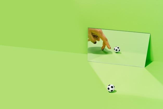 Hand van een onbekende vrouw die speelt met een voetbal op een groene achtergrond met een spiegel. voetbal en sportconcept.