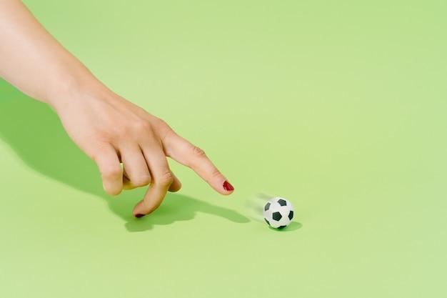 Hand van een onbekende vrouw die speelt met een voetbal op een groene achtergrond. voetbal en sportconcept.