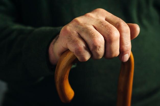 Hand van een oude man gemarkeerd in duisternis