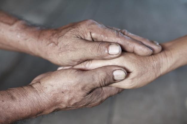 Hand van een oudere vrouw die de hand van een oudere man houdt.