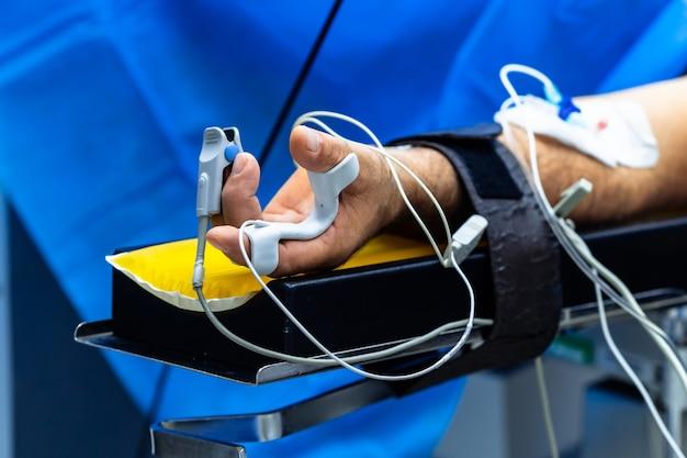 Hand van een patiënt die op de operatietafel ligt. pulsoximetersensor op de vinger. de patiënt slaapt onder algehele narcose.