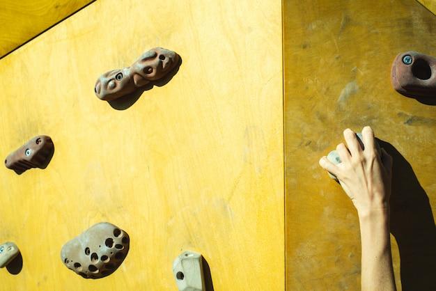 Hand van een persoon die de fixie van een klimmuur probeert te beklimmen