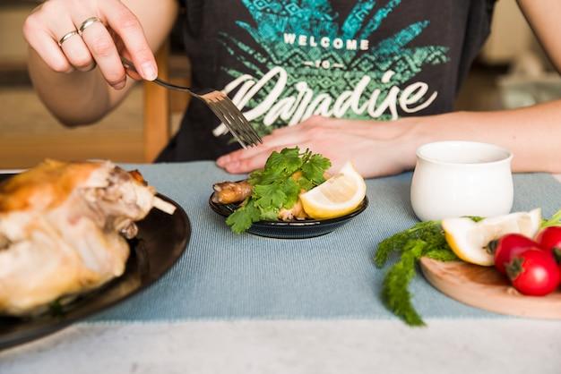Hand van een persoon die vork gebruiken terwijl het eten van geroosterde kip in diner
