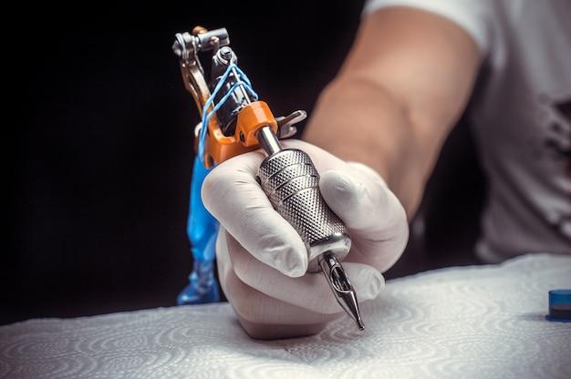 Hand van een professionele tattoo-artiest met een tattoo-machine