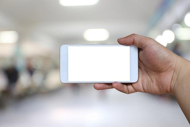 Hand van een smartphoneapparaat van de mensenholding op het onduidelijk beeldziekenhuis.