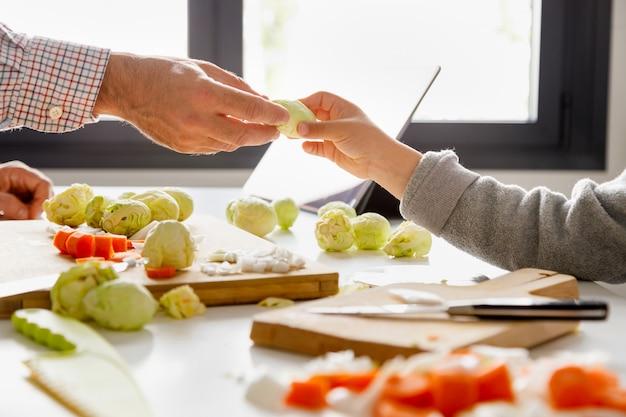 Hand van een vader die zijn dochter een spruitje geeft terwijl samen het koken