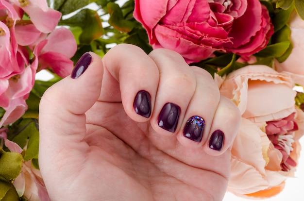 Hand van een volwassen vrouw met gelakte nagels