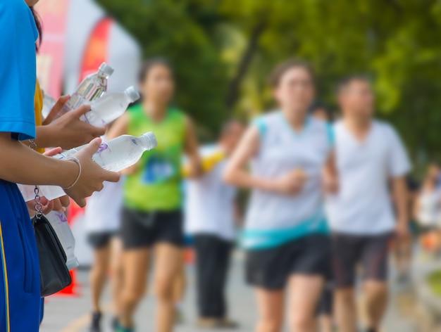 Hand van een vrijwilliger geven van water marathonlopers lopen op straat