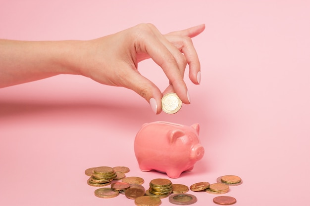 Hand van een vrouw die een één euro muntstuk opneemt in een roze ceramisch spaarvarken