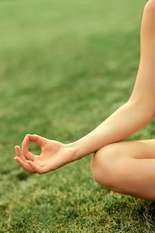 Hand van een vrouw die in lotusbloempositie mediteert die yoga in de zomer beoefent
