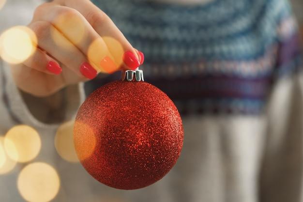 Hand van een vrouw in feestelijke trui met kerstbal met wazig licht close-up