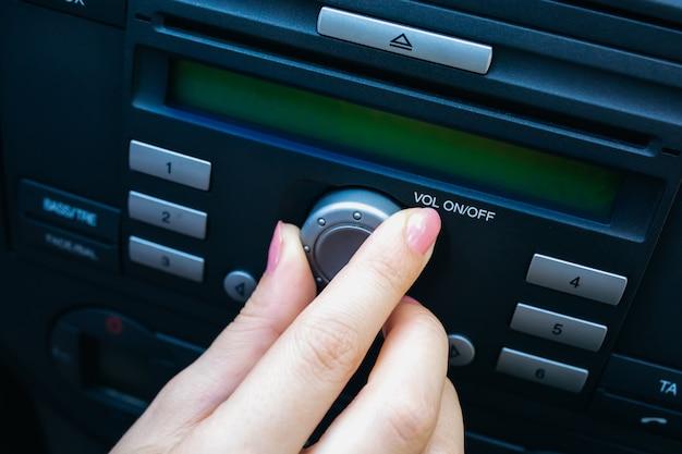 Hand van een vrouw zet het radiovolume in de auto aan