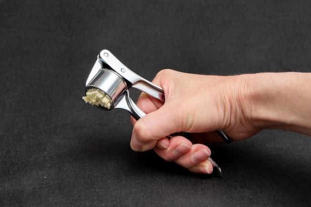 Hand van een vrouwelijke kok perst knoflook in een metalen pers op een zwarte achtergrond, close-up.