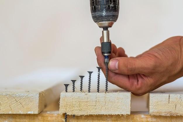 Hand van een werknemer schroeven een schroef in een houten plank met een draadloze schroevendraaier.