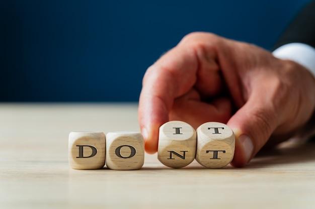 Hand van een zakenman die de laatste twee woorden van dont sign wegknipt om er een do it-bericht van te maken.