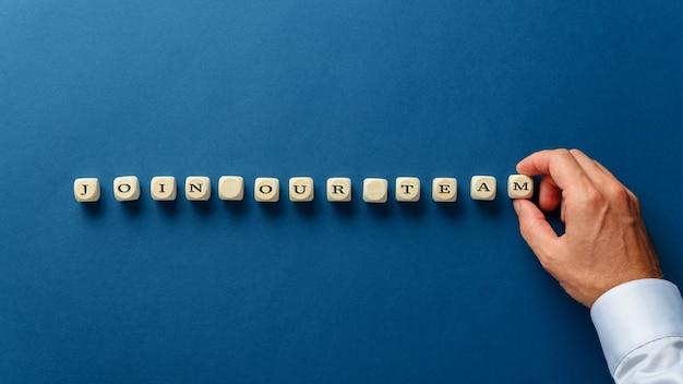 Hand van een zakenman die een bord bij ons team assembleert met houten dobbelstenen op een marineblauwe achtergrond.