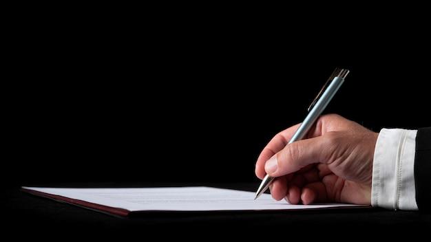 Hand van een zakenman die een document of contract op zwart bureau ondertekent op zwarte achtergrond.