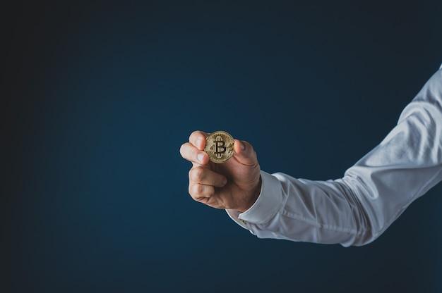 Hand van een zakenman die een gouden muntstuk van cryptovaluta bitcoin houdt.