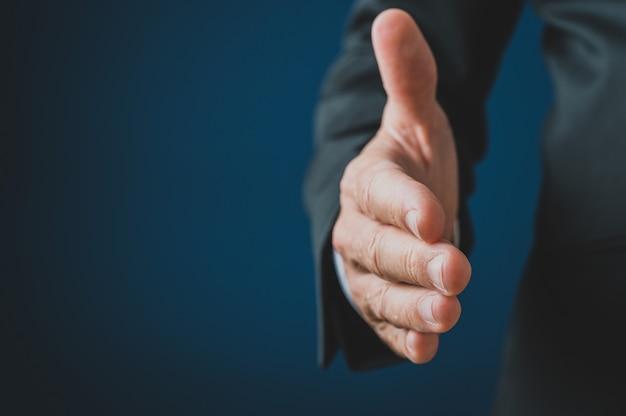Hand van een zakenman die in handdruk bereikt