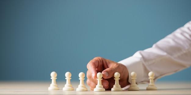 Hand van een zakenman die witte pionschaakstukken op een bureau over blauwe achtergrond plaatst.