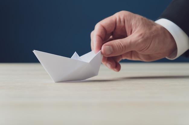 Hand van een zakenman met wit origamipapier maakte boot in een conceptueel beeld van bedrijfsvisie.
