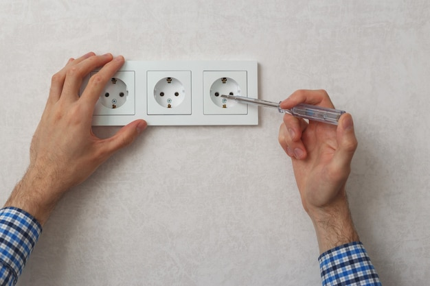 Hand van elektricien die fasetester schroevendraaier gebruikt om stopcontact te repareren.