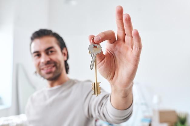 Hand van gelukkige jonge mannelijke kolonist of koper van nieuw huis of flat die u de sleutel toont terwijl u in woonkamer staat