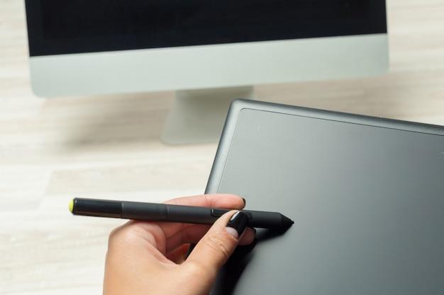 Hand van grafisch ontwerper die met stilus en tablet werkt