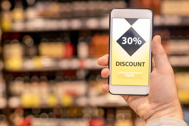 Hand van hedendaagse klant die mobiele app toont die u een goede korting geeft voor het aantal voedselproducten in de supermarkt