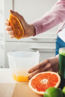 Hand van het meisje dat een sinaasappel knijpt en thuis vers vruchtensap maakt