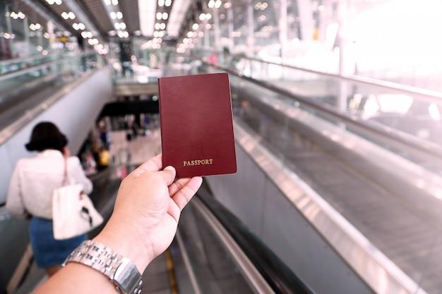 Hand van het paspoort van de mensenholding bij luchthaven, plastic roze toon.