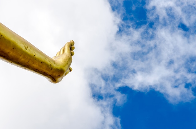 Hand van het standbeeld van boedha op blauwe hemel