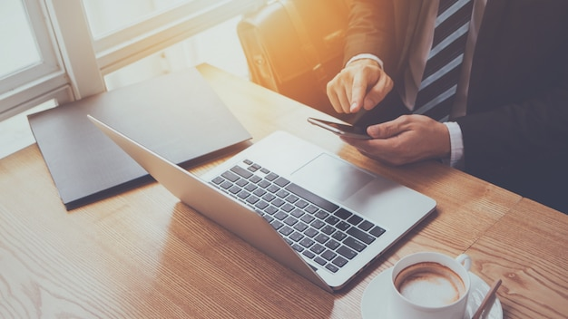 Hand van het typen van de zakenman op smartphone met laptop en koffiekop