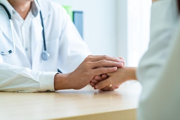 Hand van hogere arts die haar vrouwelijke patiënt geruststelt