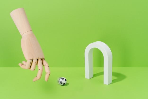 Hand van hout spelen met een voetbal op een doel op een groene achtergrond. voetbal en sportconcept.