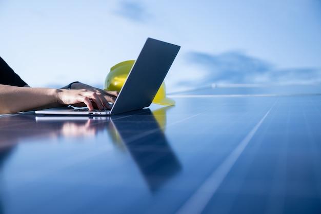 Hand van ingenieur die notebook gebruikt op fotovoltaïsche elektriciteitscentrale op het dak voor het analyseren van elektrische gegevens, groene energie en duurzaam wereldconcept.